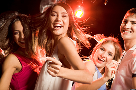Pretty clubber dancing surrounded by her friends and looking at camera with smile; Shutterstock ID 20501615; PO: aol; Job: production; Client: drone